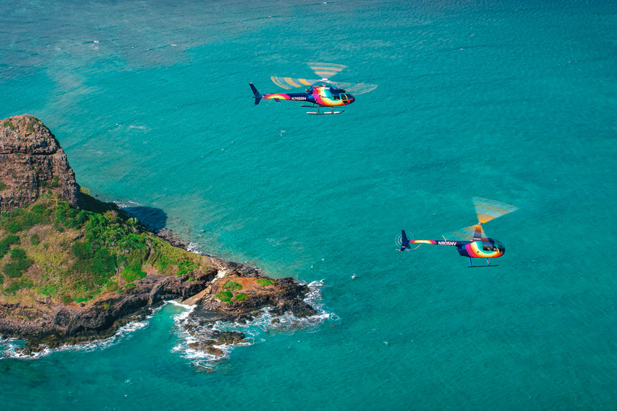 Two Rainbow Helicopters flying over blue ocean water with an small island