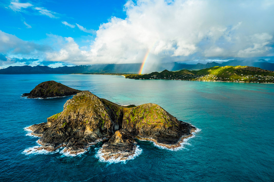 Rainbow from cloud to the land with blue ocean water and green islands, Oahu