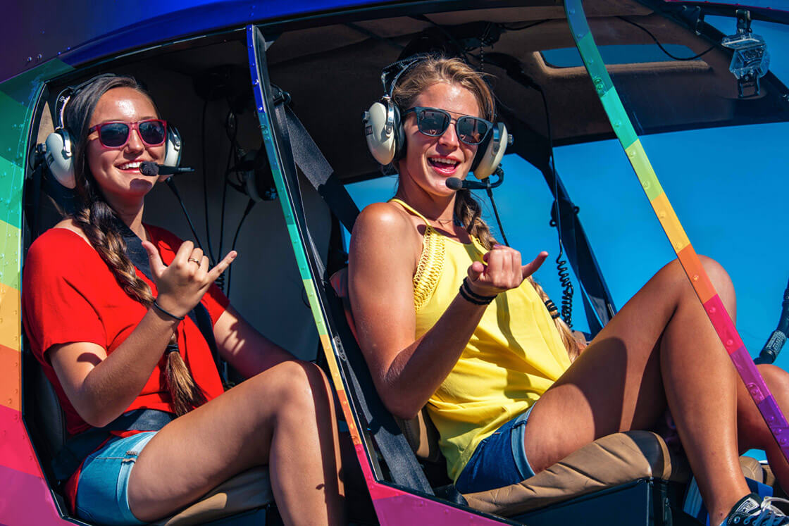 Rainbow Oahu Helicopter Tours - Young Women Smiling In A Rainbow Helicopter